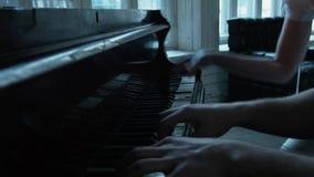 Um homem em uma grande janela joga o piano, uma jovem mulher ajuda-o pressionando as chaves vídeos de arquivo