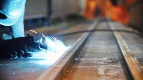 Um homem em uma m?scara protetora queima-se atrav?s do elemento do ferro com uma m?quina de solda video estoque