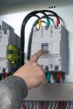 Um homem em uma mão cinzenta do pulôver fora do interruptor de poder é instalado no armário bonde Elét. conectado interruptor fotos de stock royalty free