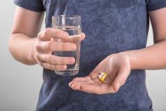 Um homem em uma obscuridade - o t-shirt azul está guardando diversas comprimidos e cápsulas, e um vidro grande da água em um fund Foto de Stock Royalty Free