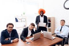 Um homem em uma peruca veio a uma reunião de negócios Fotografia de Stock Royalty Free