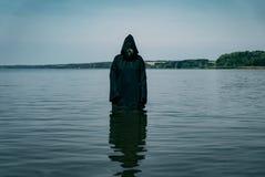 Um homem em uma veste preta com uma capa está no rio durante o dia Olha misteriosamente a água imagens de stock royalty free