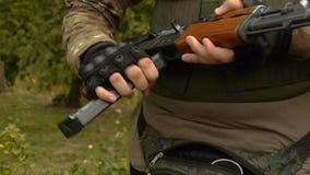 Um homem em um uniforme com uma arma em suas mãos, soldado com espingarda automática filme