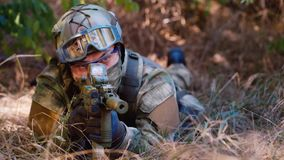 Um homem em uniformes da camuflagem encontra-se na terra, escondendo nos arbustos Visando armas vídeos de arquivo
