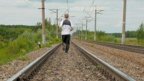 Um homem em uniformes dos esportes corre nos trilhos Segue sua saúde, corre o estilo de vida transversal, ativo filme
