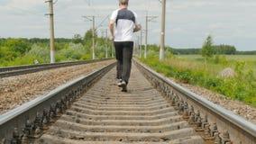 Um homem em uniformes dos esportes corre nos trilhos Segue sua saúde, corre o estilo de vida transversal, ativo video estoque