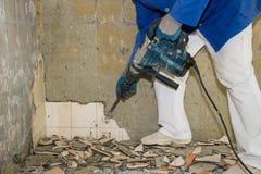 Um homem embala telhas com um martelo da demolição foto de stock royalty free