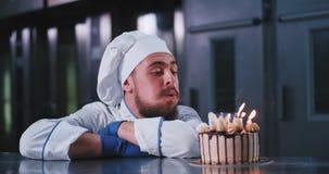 Um homem encantador com um chapéu dos cozinheiros chefe funde para fora as velas em um bolo de aniversário divino vídeos de arquivo