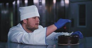 Um homem encantador enfrentado carnudo do padeiro tomou a cereja vermelha de um bolo e a vista dele está sendo fascinado video estoque
