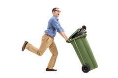 Um homem entusiasmado que empurra uma lata de lixo Imagem de Stock