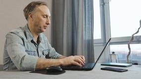 Um homem envelhecido médio que trabalha em um portátil O Freelancer trabalha em casa filme