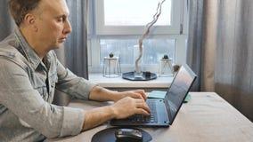 Um homem envelhecido médio que trabalha em um portátil O Freelancer trabalha em casa Vista lateral filme