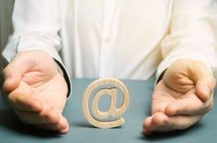 Um homem envolve suas mãos em torno de uma figura da vara do e-mail e do Internet O conceito de salvar o Internet é aberto e inde imagens de stock