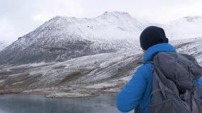 Um homem escalado altamente nas montanhas, exulta e comemora sua vitória, levanta suas mãos acima na frente dele é video estoque