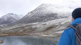 Um homem escalado altamente nas montanhas, exulta e comemora sua vitória, levanta suas mãos acima na frente dele é vídeos de arquivo