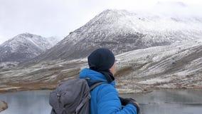 Um homem escalado altamente nas montanhas, exulta e comemora sua vitória, levanta suas mãos acima na frente dele é filme