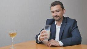 Um homem escolhe entre vidros do vinho e leite vídeos de arquivo