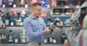Um homem escolhe um misturador nos dispositivos de cozinha da loja de dispositivos em suas mãos e considera o projeto e video estoque