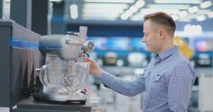 Um homem escolhe um misturador nos dispositivos de cozinha da loja de dispositivos em suas m?os e considera o projeto e vídeos de arquivo