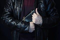 Um homem esconde uma bolsa do ` s da mulher em seu peito, o roubo de uma bolsa, um fundo preto, roubo dos sacos fotografia de stock