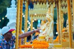 Um homem espirra a estátua da Buda com o perfume fotografia de stock royalty free
