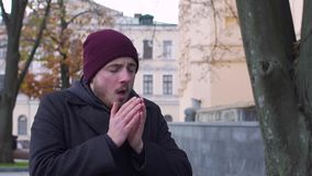 Um homem espirra na rua, tiro do lento-movimento video estoque