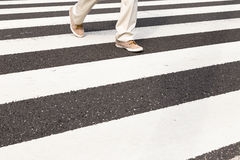 Um homem está andando no cruzamento de zebra Imagem de Stock