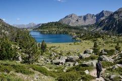 Caminhante que desce ao lago montanhoso imagens de stock royalty free