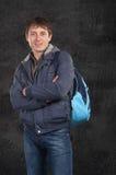 Um homem está com uma trouxa em seu ombro Fotos de Stock Royalty Free