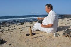 Um homem está comemorando com um vidro do vinho na praia Imagem de Stock