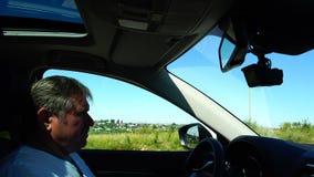 Um homem está conduzindo em campos e em vilas de um verde do passado do carro video estoque