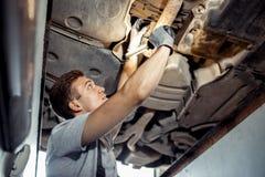 Um homem está conduzindo um exame detalhado de um carro levantado na imagem de stock royalty free