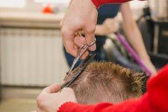 Um homem está cortando um menino Foto de Stock Royalty Free