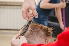 Um homem está cortando um menino Fotografia de Stock Royalty Free