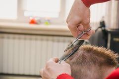 Um homem está cortando um menino Imagens de Stock