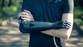 Um homem está cruzando seu braço artificial com saudável Conceito humano do cyborg