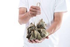 Um homem está dando a bolinha de massa do zongzi ou do arroz a outro como um presente ou uma lembrança em Dragon Boat Festival, a imagens de stock