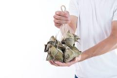 Um homem está dando a bolinha de massa do zongzi ou do arroz a outro como um presente ou uma lembrança em Dragon Boat Festival, a imagem de stock royalty free