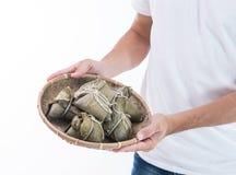 Um homem está dando a bolinha de massa do zongzi ou do arroz a outro como um presente ou uma lembrança em Dragon Boat Festival, a foto de stock royalty free
