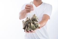 Um homem está dando a bolinha de massa do zongzi ou do arroz a outro como um presente ou uma lembrança em Dragon Boat Festival, a fotografia de stock royalty free