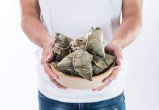 Um homem está dando a bolinha de massa do zongzi ou do arroz a outro como um presente ou uma lembrança em Dragon Boat Festival, a imagens de stock royalty free