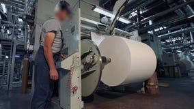 Um homem está em uma fábrica para a produção de papel de parede Um homem na fábrica controla a máquina video estoque