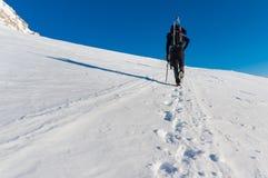 Um homem está escalando a montanha coberta com a neve com seus esquis em sua trouxa Fotos de Stock Royalty Free