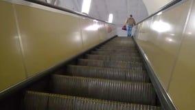 Um homem está escalando uma escada rolante à saída à estação de metro de Belorusskaya vídeos de arquivo