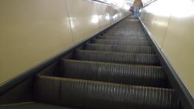 Um homem está escalando uma escada rolante no metro video estoque