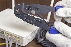 Um homem está espremendo uma microplaqueta em um cabo da rede, um modem, o Internet, um roteador do close-up fotos de stock
