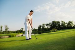 Um homem está estando em um campo de golfe e está preparando-se para bater a bola com um clube de golfe imagens de stock
