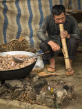 Um homem está fumando uma grande tubulação atrás de uma grande bandeja com carne no mercado da manhã de Bac Ha Foto de Stock