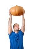 Um homem está guardando a abóbora grande acima da cabeça Imagem de Stock Royalty Free