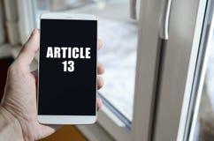 Um homem está guardando um smartphone com inscrição do artigo 13 imagem de stock